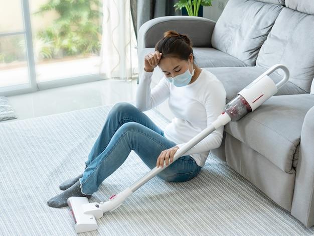 家の掃除機を使用した後、床に座っている女性。
