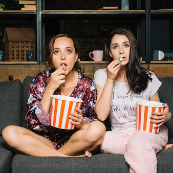 Women sitting on sofa staring while watching television