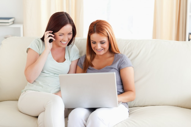 Women sitting on a sofa with a laptop and a phone in a living room
