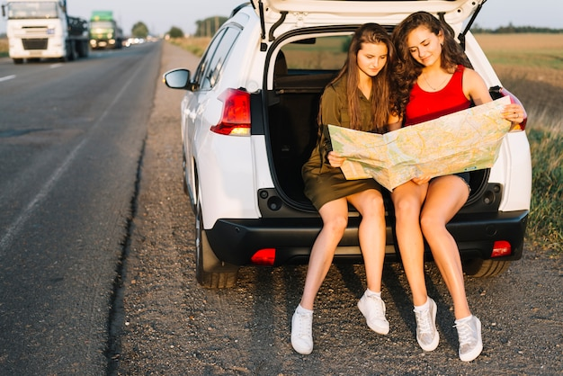 Women sitting on white car with map
