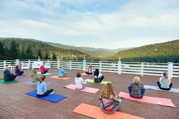 Women sitting on yoga mats in mountains, practicing.