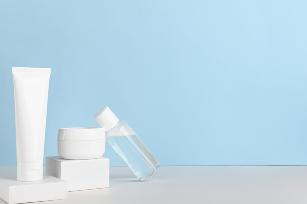 파란색 배경에 여성 스킨 케어 제품 빈 패키지 구성.