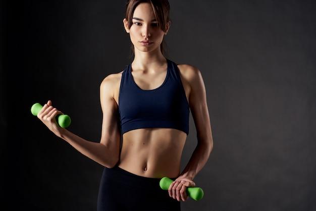 女性のスリムな体型の緑のダンベルは、トレーニングの動機を行使します