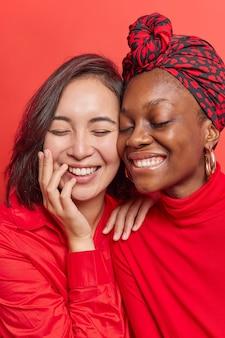 女性は歯で喜んで微笑む素敵な一日を楽しんでいますお互いに密接に立って鮮やかな赤で積極的に孤立して笑う