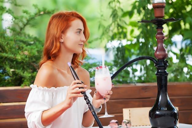 여성들은 길거리 카페에서 물 담뱃대를 피 웁니다.