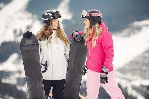 Women in snowboard suit. sportswomen on a mountain with a snowboard in hands on the horizon. concept on sports