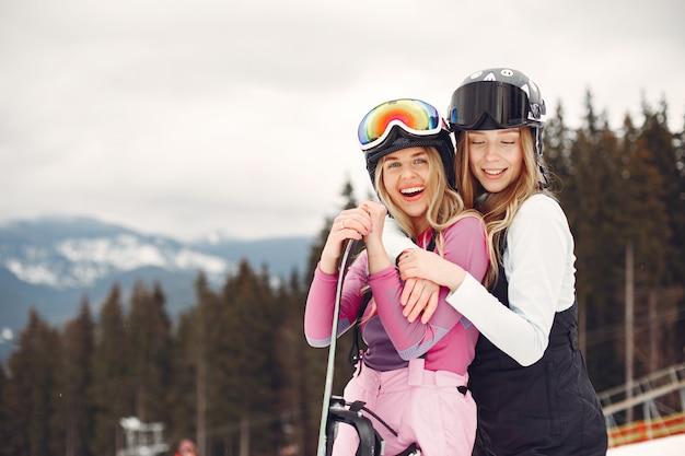 Donne in tuta da snowboard. sportive su una montagna con uno snowboard in mano all'orizzonte. concetto di sport