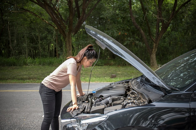 Women spection she opened the hood broken car on the side see engines that are damaged or not