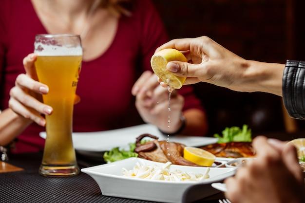 문자열 치즈 맥주 간식 위에 레몬을 짜는 여자
