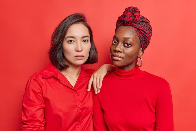 여성들은 서로 가까이 서서 빨간 옷을 입은 카메라를 차분하고 자신감 있게 바라보며 스튜디오에서 자연스러운 아름다움을 지닌 건강한 피부 포즈를 취합니다. 다양한 레즈비언 여성