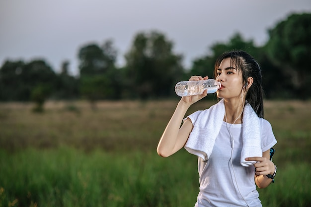 Women stand to drink water after exercise