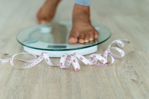 여성들은 체중 조절이 필요한 측정 케이블을 들고 전자 저울 위에 서 있습니다. 여자 발은 줄자로 체중계를 밟습니다. 다이어트 개념