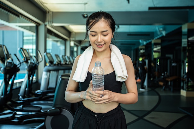Women stand and relax after exercising, holding and looking at the water bottle.