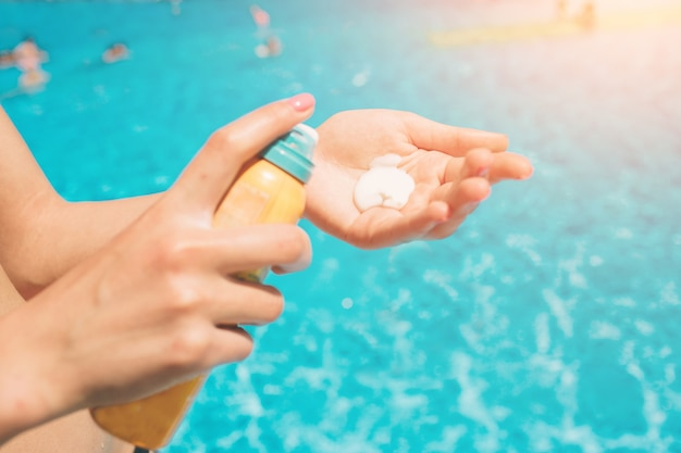 Women standing on the beach and using suncream. close up of women hands receiving sunblock cream lotion