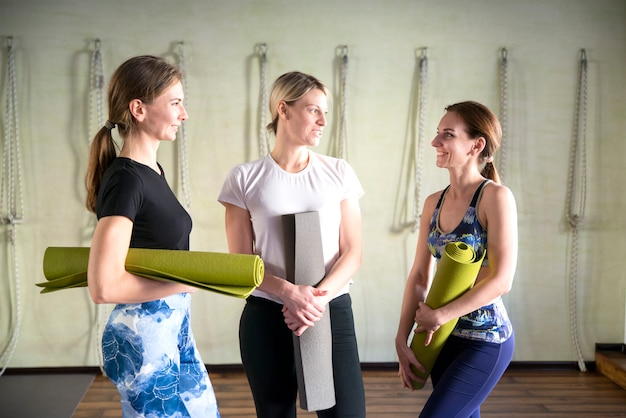 Women standing by a wall with exercise mats
