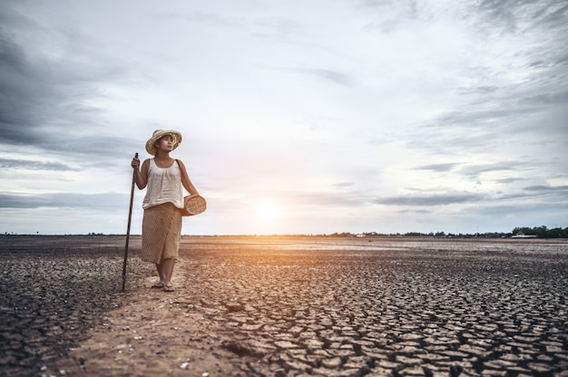 Women standing on dry soil and fishing gear, global warming and water crisis