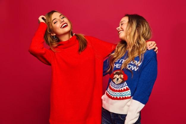 Женщины, стоящие в стильных зимних теплых свитерах на красной стене