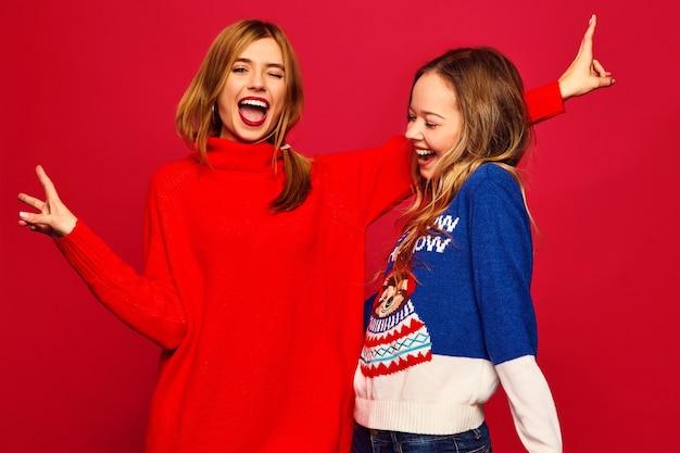 赤い壁にスタイリッシュな冬の暖かいセーターに立っている女性