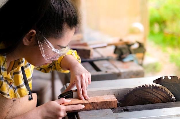 立っている女性は、丸鋸電動工具を備えた作業台でカットウッドを加工する工芸品です