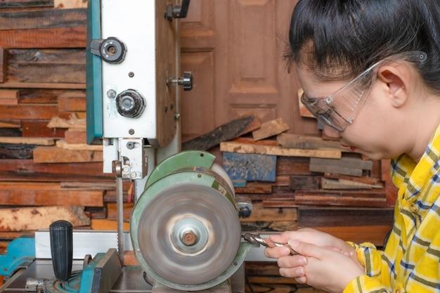 숫돌 기계 전동 공구로 작업대에서 드릴을 갈고 있는 여성
