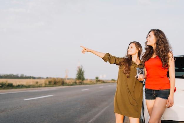 Женщины, стоящие рядом с автомобилем и глядя в сторону