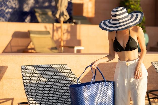 ビーチで日光浴用のストローバッグが付いている日光浴ベッドの近くに立っている女性。