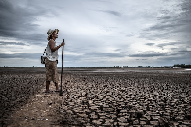 乾燥した土壌と漁具の上に立っている女性、地球温暖化と水危機