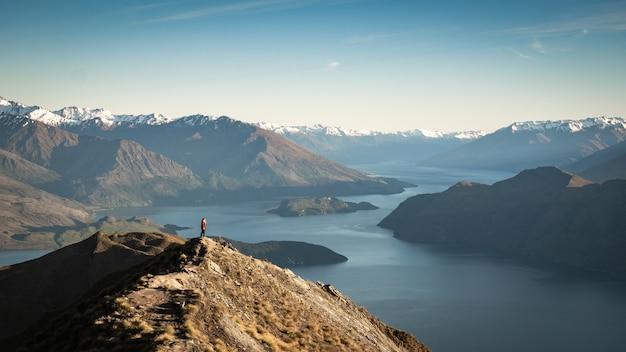 ニュージーランドの湖と山々の景色を楽しみながら山頂に立つ女性たち