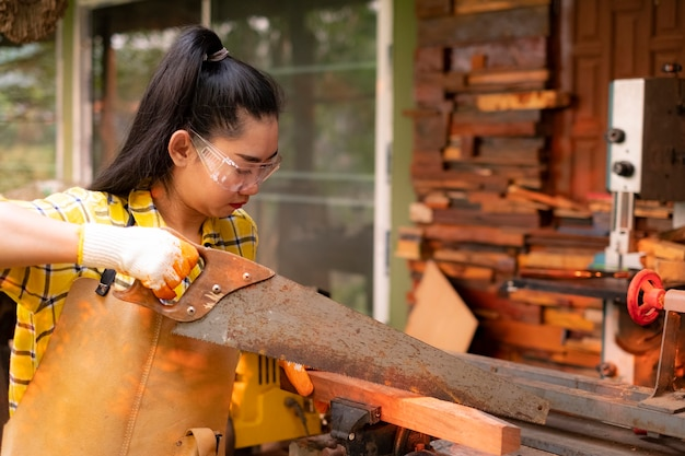バリの背景に木の板を鋸で立っている女性