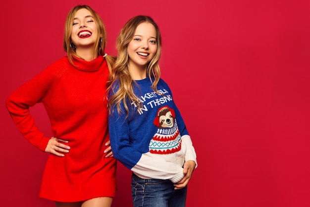 Women standing in stylish winter warm sweaters on red wall