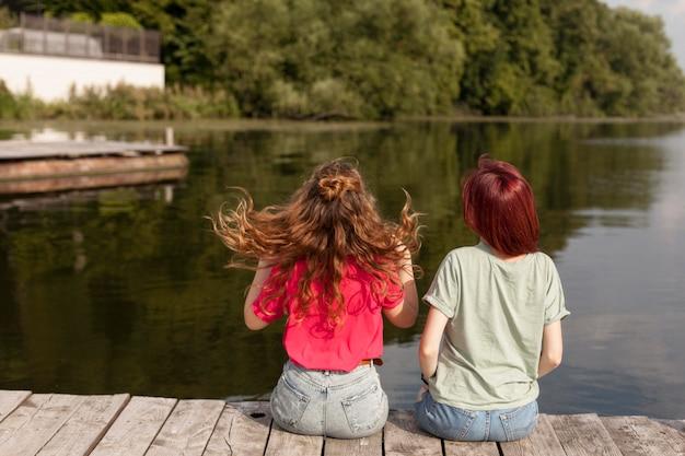 Le donne che soggiornano in banchina guardando il lago