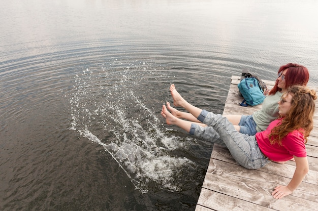 Women staying on dock and splashing water with their feet+