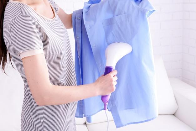 部屋でシャツを蒸している女性