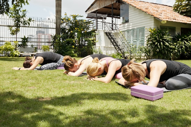 Women stretching on green grass outdoors with their heads resting on hands in a child pose