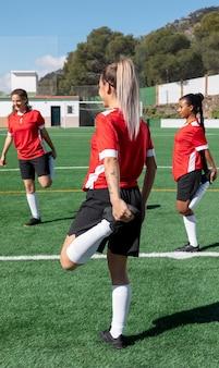 Женщины растягивают ногу на футбольном поле