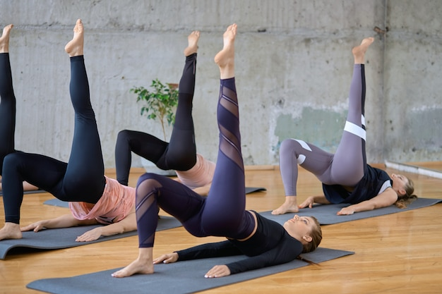 Women stretching with leg up on mats.
