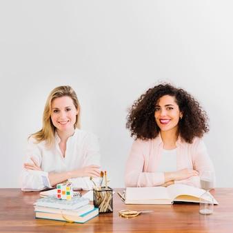 Женщины, изучающие и смотрящие на камеру