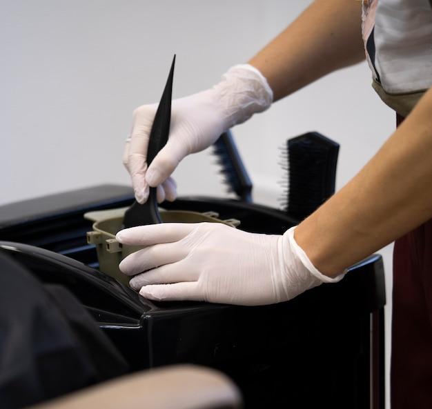 Стилист женщин в перчатках готовит цветной крем для окрашивания волос в контейнере, маску для лечебной процедуры в салоне красоты. парикмахер, смешивая кисть, окрашивая волосы концепции поставок. копирование пространства спа