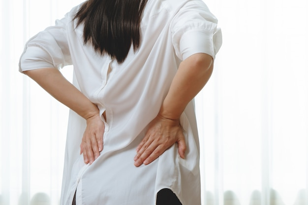 Women suffer from back pain at home.