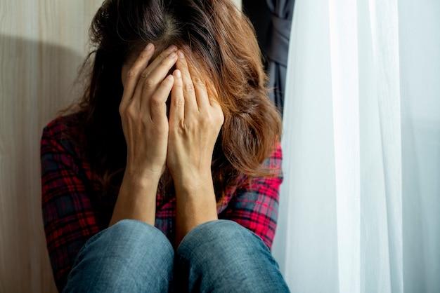 うつ病に苦しむ女性窓際の顔に手をかざして泣きながら座っていると、不幸なネガティブな問題感に不安を感じる