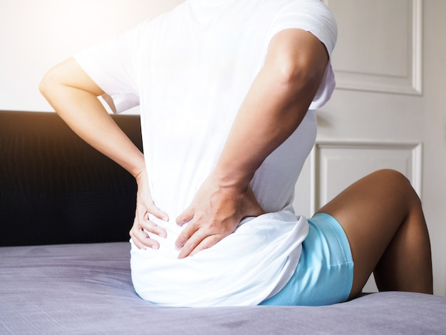 Women suffering with back pain and waist pain sitting on bed.