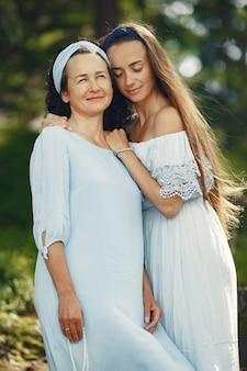 Donne in una foresta estiva. signora in un vestito blu. famiglia in posa e abbraccio.