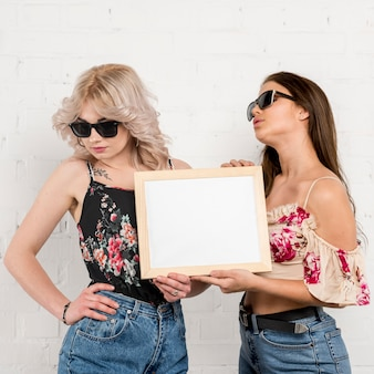 Women in sunglasses holding empty paper in hands