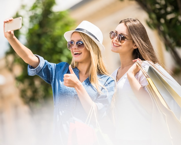 Women in sunglasses taking a selfie with their cell phone.
