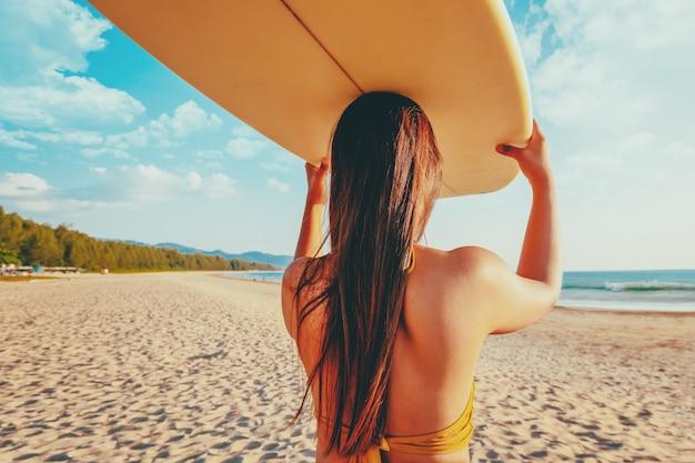 ビーチでサーフボードを持つ女性サーファー