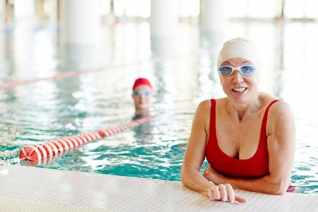 スイミングプールで泳いでいる女性
