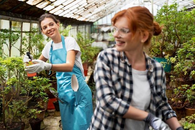Donne che si prendono cura delle loro piante in una serra