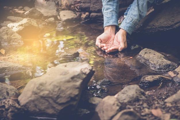 Женщины, принимающие чистую воду в малом потоке