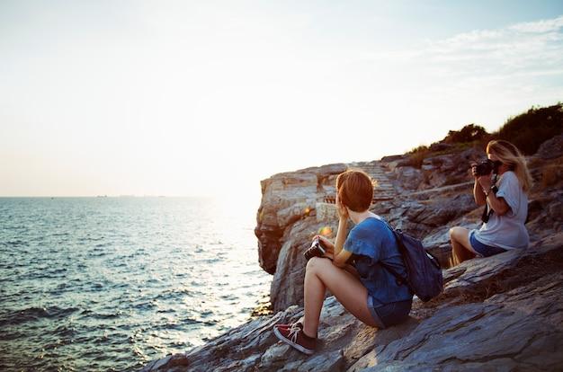 Women taking photo by seashore