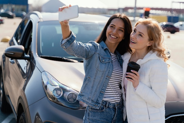 Women taking a selfie next to a car